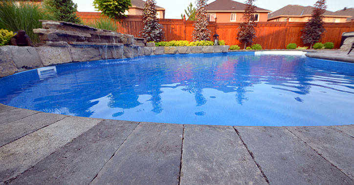 low-angle photo of pool with stone water feature
