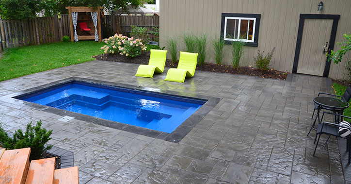 small wading pool with lounge chairs near
