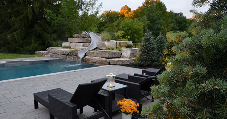 black lounge chairs next to pool with slide