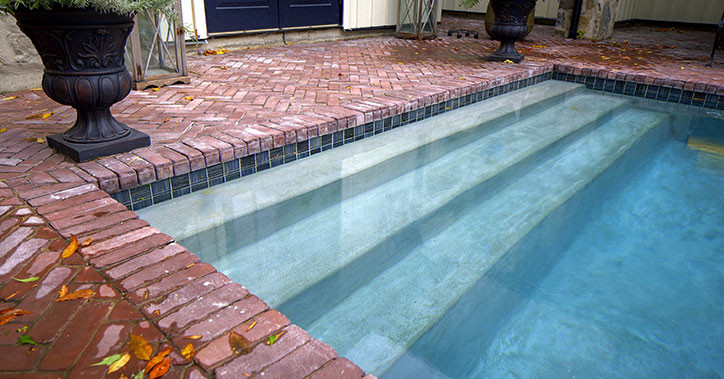 concrete pool with red brick surround