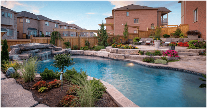 landscaped back yard with stone and pool