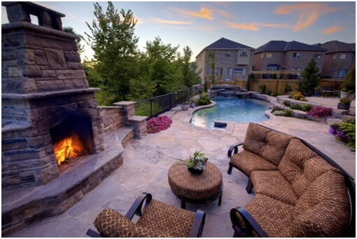 fireplace and patio furniture near pool