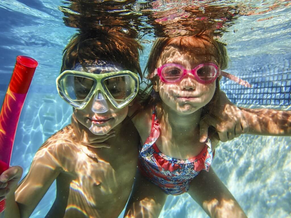 little boy and girl with goggles under water in a pool