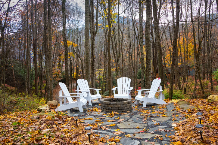 stone patio with white muskoka chairs in fall