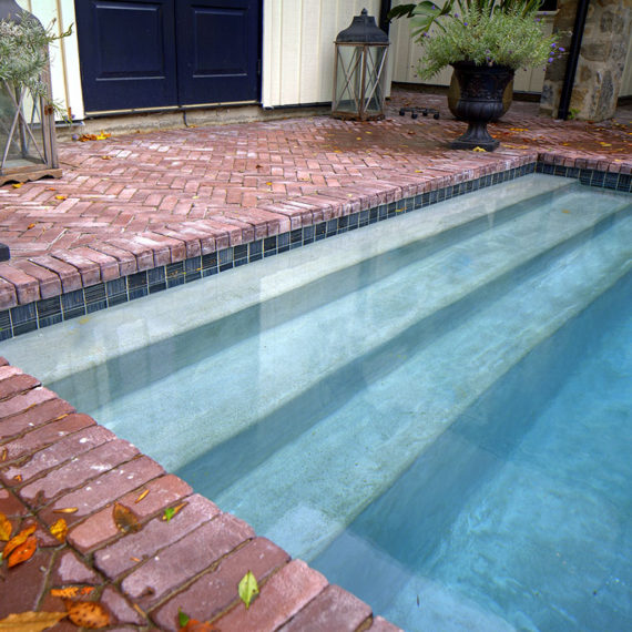 detail photo of concrete steps in brick-surrounded pool