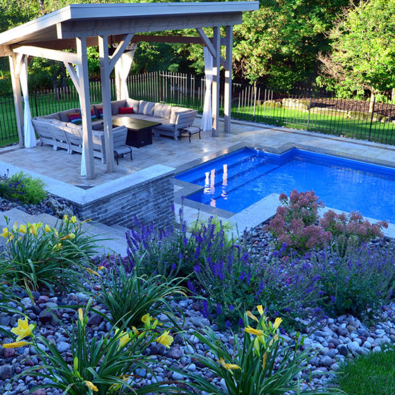 backyard pool with cabana and landscaping