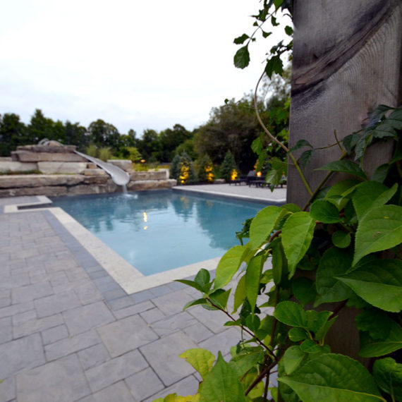 large rectangular pool with stone feature and water slide