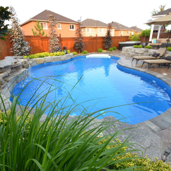 pool with printed concrete and water feature featuring landscaping