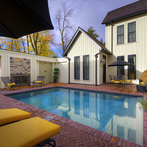 brick-surrounded rectangular pool and wood-panel house