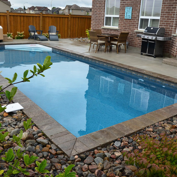 photo of backyard pool looking towards brick house
