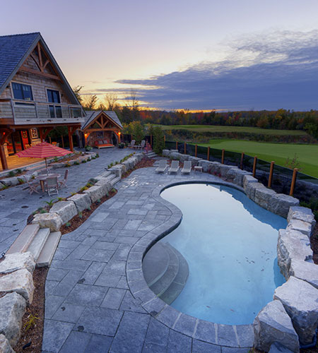 outdoor pool with stone surround bordering a golf course