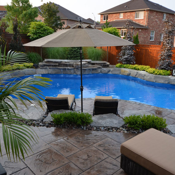 two lounge chairs and an umbrella facing an outdoor pool