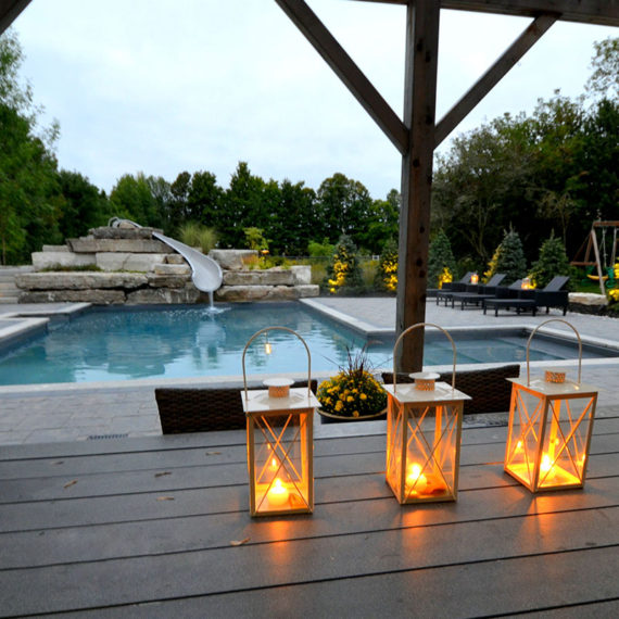 candles on a deck near a pool with a water slide