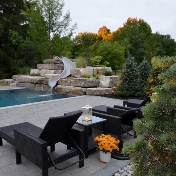 outdoor pool with black lounge chairs and water slide
