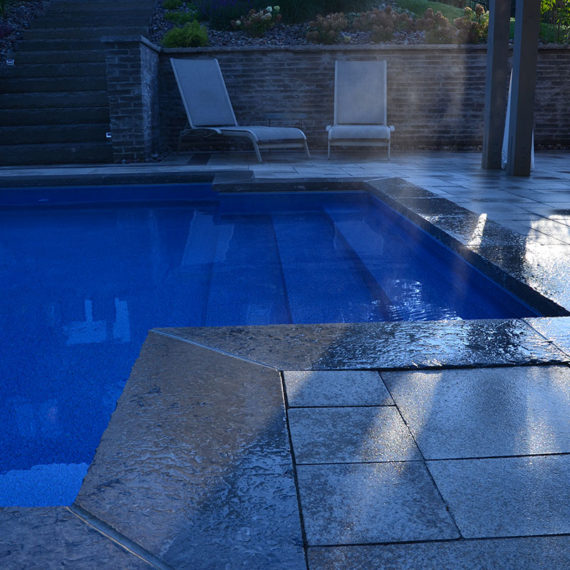 outdoor pool with stone surround and scattered sunlight
