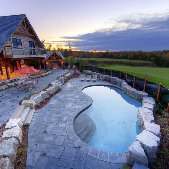 outdoor pool with stone surround bordering golf course