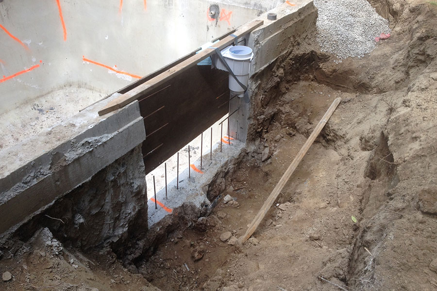 cut concrete pool wall being repaired