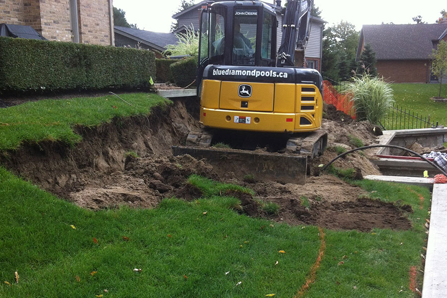 excavator moving earth for pool renovation